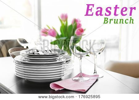 Text EASTER BRUNCH on background. Clean dishware on table