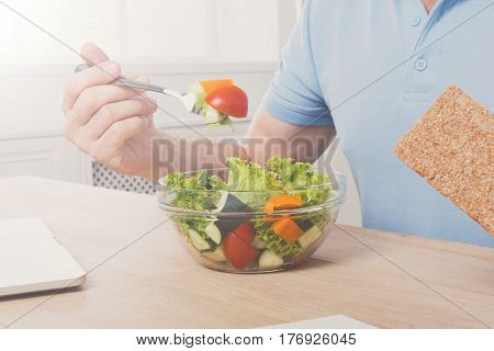 Healthy business lunch in office concept. Businessman in t-shirt at working place has vegetable salad in bowl, diet and eating right concept.