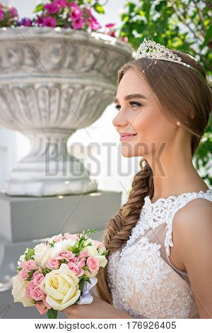 Portrait of a beautiful bride, smiles, a bouquet of a bride and a diadem