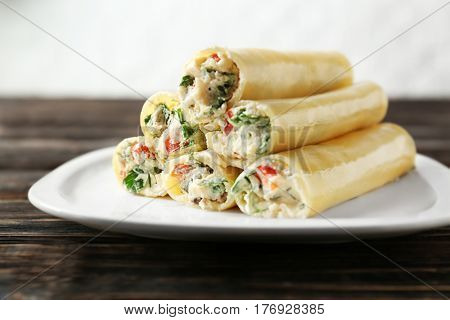Delicious stuffed cannelloni in plate on wooden table