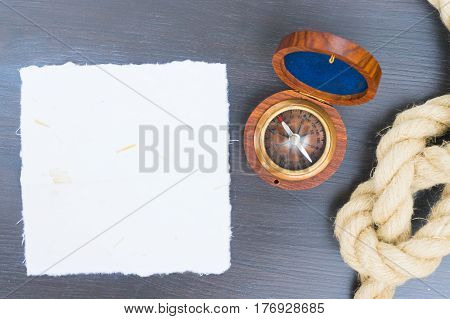 Old vintage compass with rope, copy space on white paper