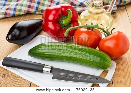 Different Vegetables, Bottle Of Oil, Cutting Board And Knife