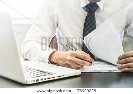 Close up of Businessman checking document on the desk.