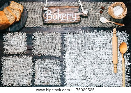 Rustic style template for food and drink industry. Burlap frames on dark wood background with flour pack and sliced bread. Wooden  signboard with text 'Bakery' as title bar