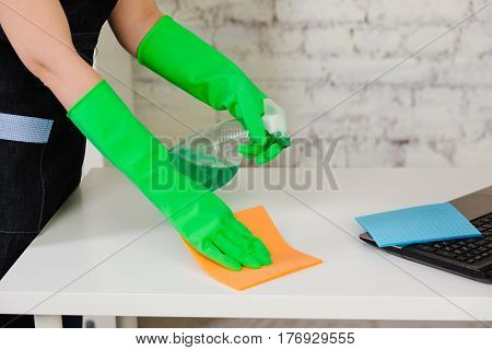 cleaner hands dressed in protective gloves spraying detergent on the sponge and cleaning table, close-up. Professional cleaning of home