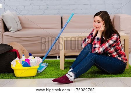 tired housewife dressed in casual clothes sitting on the floor, during household chores. Beside her cleaning supplies, mop for cleaning the house.