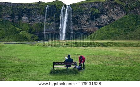 famous Skogarfoss waterfall in southern Iceland. The traveler sits on a bench and looks at the waterfall. treking in Iceland. Travel and landscape photography concept