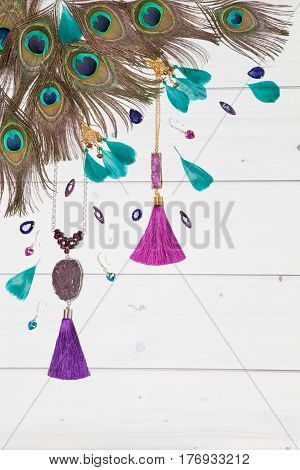 Handmade turquoise and violet bijouterie with gems tassels and peacock feathers in boho style lying flat on the white wooden vertical background top view diagonal composition.