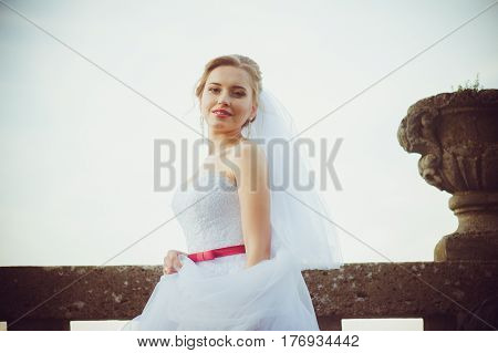 Beautiful bride walking near old castle before ceremony