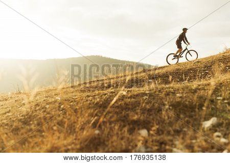 Side view of an unrecognizable person riding a trial bike in the hills. Horizontal outdoors shot.