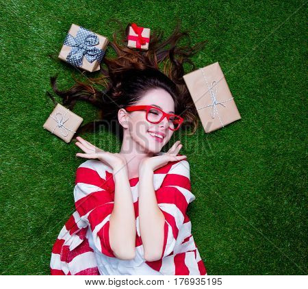 Beautiful Young Woman Near Gifts  Lying On The Wonderful Green Grass Background
