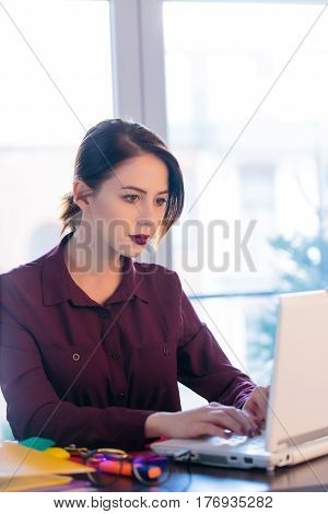 beautiful young woman sitting at the desk and working with laptop in her office