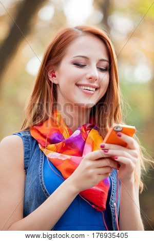 Beautiful Young Woman Holding Her Mobile Phone And Smiling On The Trees Background