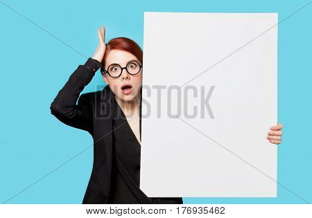 Beautiful Surprised Young Woman With Big Empty Poster On The Wonderful Blue Background