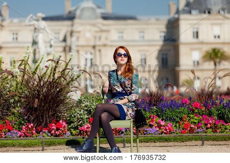 beautiful young woman sitting on the chair near flowerbed on the mansion background