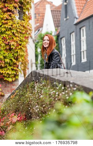 Beautiful Young Woman Standing Near The Stone Fence And Exploring The Town