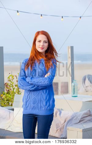 beautiful young woman standing in the cafe on the beach