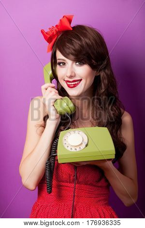 photo of beautiful young woman with retro phone on the wonderful purple background