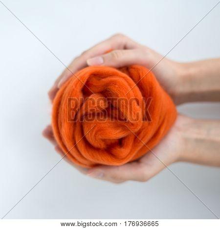 Close-up of orange merino wool ball in hands.