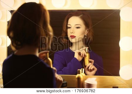 photo of beautiful young woman holding her perfume near the window with lights