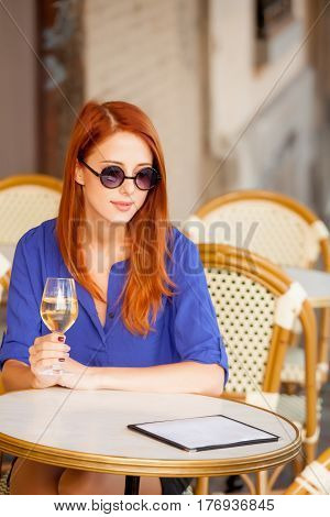 Beautiful Young Woman Sitting In The Cafe And Holding Glass Of Champagne