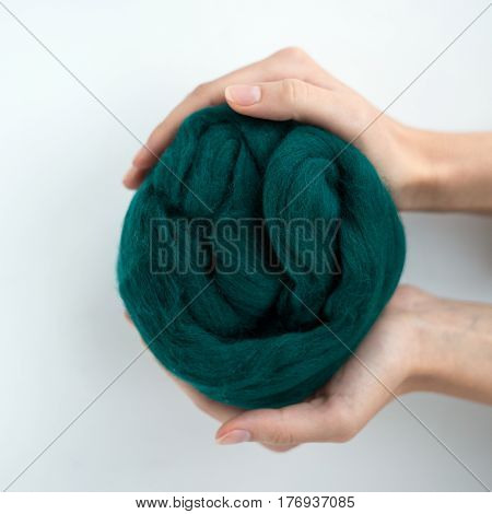 Close-up of grey merino wool ball in hands.