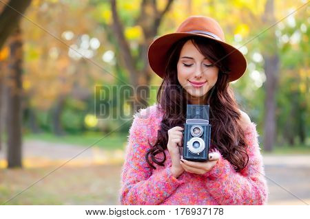 Photo Of Beautiful Young Woman Standing In The Park With Retro Camera