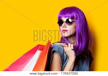 Photo Of Beautiful Young Woman In Wig With Shopping Bags On The Wonderful Yellow Background