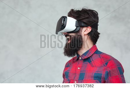 Happy bearded man wearing the VR headset and laughing. Horizontal studio shot.