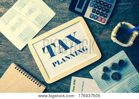 whiteboard with Tax planning text layout with a calculator. Passbook tax form and coins on wooden table for planning Money Financial Accounting Concept