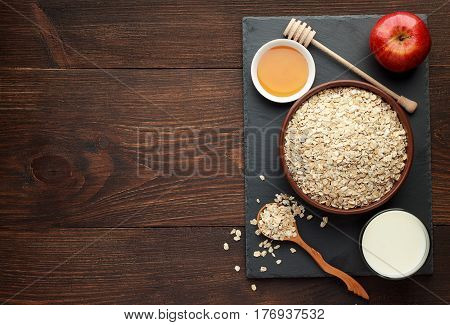 Bowl of oat flakes with honey apple and milk on wooden background. Concept of healthy food. Top view copy space.