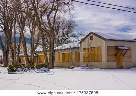 Boarded Up Commercial Building With Snow In Wintertime