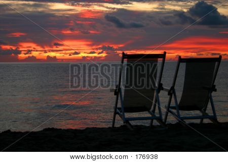Sunset & Chairs On Beach