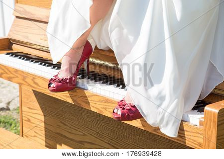 A brides red shoes rest on the keys of a piano that sits outside in the sun