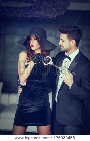 Sexy woman in hat holding rich man in tux on handcuffs