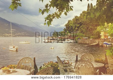 Beautiful retro toned cityscape with a Como lake coastline of italian Varenna city with building tree boats and dramatic sky before the rain