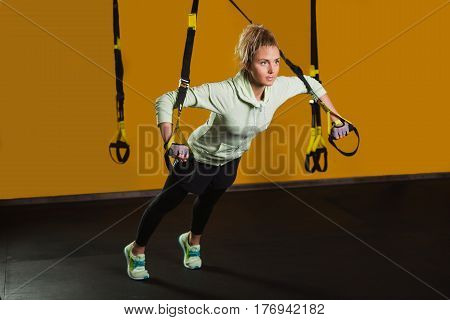 Sporty woman doing exercises using suspension strap. Intensive body training in the gym