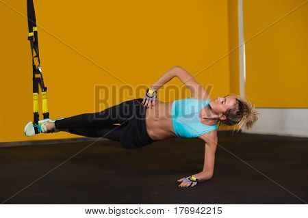 Sporty woman holding body on one hand While legs located in the suspension straps. Exercises for a slender body