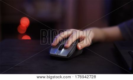 child's hand with computer mouse on dark background, close-up