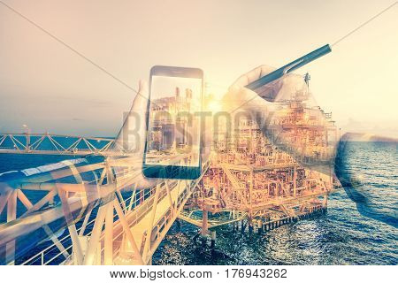 Double exposure of refinery oil and gas background and businessman on hipster shirt use mobile phone and electronic pen for oil and gas business concept.