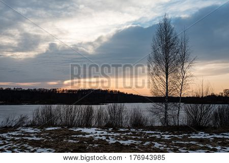 sunset over the river Daugava with dramatic colorful sky and tree silhouettes