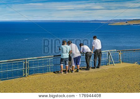 CHUBUT, ARGENTINA, MARCH - 2016 - Group of adult men watching the view at Punta del Marquez a touristic viewpoint located in Chubut Argentina.