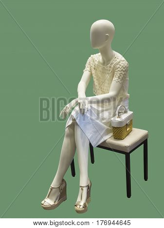 Sitting female mannequin against green background. No brand names or copyright objects.