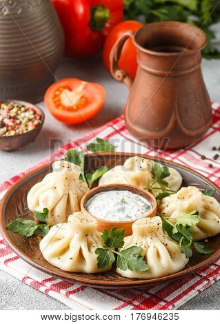 Khinkali - Georgian Dumplings With Meat And Parsley In A Ceramic Dish With A Sauce Of Sour Cream And