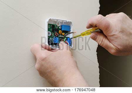 Installing a programmable room thermostat. Man's hands fixing the wires to the terminals and connects the device.