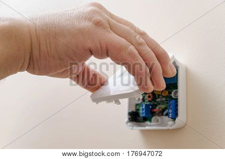 Installing a programmable room thermostat. Man's hand holding the lid of the device.