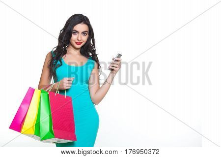 beautiful young girl with red lips smiling on a white background with a cell phone and many colorful shopping bags