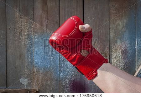 Man's hand in red boxing gloves blue wooden background outside focus