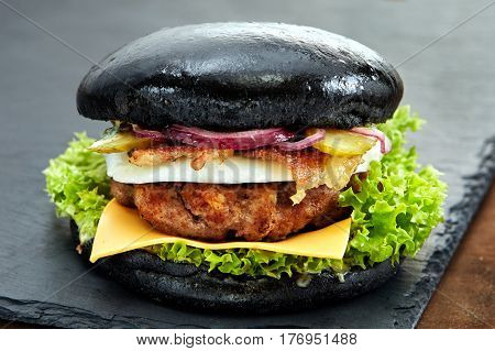Black hamburger on stone table with black background. Fastfood meal. Delicious and gourmet hamburger. Appetizing food. Hamburger with grilled meat, tomatos, cheese, pickles, onion and lettuce.
