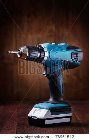 Blue cordless screwdriver with a drill on wooden table with wooden background. Tools. Home. Interior. Repair and repairs. Building. Instruments.